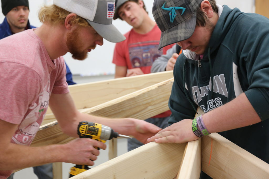 students working to stabilize roofing structure
